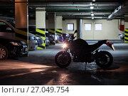 Купить «Мотоцикл стоит перед машинами в крытом темном паркинге», фото № 27049754, снято 1 октября 2017 г. (c) Кекяляйнен Андрей / Фотобанк Лори