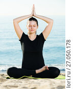 Купить «Smiling adult female in black T-shirt is sitting and practicing pranayama», фото № 27050178, снято 15 мая 2017 г. (c) Яков Филимонов / Фотобанк Лори