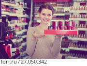 Купить «Young female seller is demonstrating nail lacquer», фото № 27050342, снято 21 февраля 2017 г. (c) Яков Филимонов / Фотобанк Лори