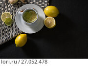 Купить «Tea cup with lemon on black background», фото № 27052478, снято 12 июня 2017 г. (c) Wavebreak Media / Фотобанк Лори