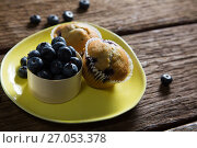 Купить «Blueberries and muffins on plate», фото № 27053378, снято 12 июня 2017 г. (c) Wavebreak Media / Фотобанк Лори