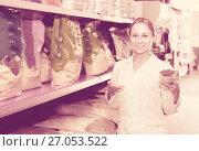 Купить «Glad shop assistant offers to choose pet food», фото № 27053522, снято 24 января 2020 г. (c) Яков Филимонов / Фотобанк Лори