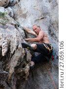 Купить «Мужчина скалолаз со снаряжением сосредоточенно поднимается вверх по отвесной горной скале», фото № 27059106, снято 15 декабря 2010 г. (c) Эдуард Паравян / Фотобанк Лори