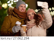 Купить «couple with coffee taking selfie at christmas», фото № 27062294, снято 2 декабря 2016 г. (c) Syda Productions / Фотобанк Лори