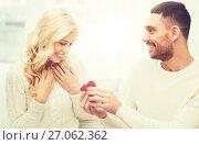 Купить «happy man giving engagement ring to woman at home», фото № 27062362, снято 8 октября 2015 г. (c) Syda Productions / Фотобанк Лори