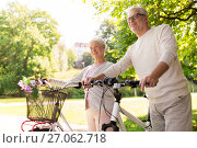 Купить «happy senior couple with bicycles at summer park», фото № 27062718, снято 9 августа 2017 г. (c) Syda Productions / Фотобанк Лори