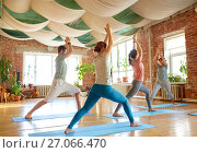 Купить «group of people doing yoga warrior pose at studio», фото № 27066470, снято 5 марта 2017 г. (c) Syda Productions / Фотобанк Лори