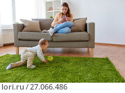 Купить «mother with smartphone and baby playing at home», фото № 27066486, снято 19 мая 2017 г. (c) Syda Productions / Фотобанк Лори