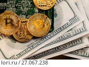 Купить «Золотые монеты криптовалюты Биткоин лежат на сто-долларовых пачках денег», фото № 27067238, снято 9 октября 2017 г. (c) Николай Винокуров / Фотобанк Лори