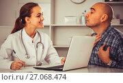 Купить «Male visitor consulting smiling woman doctor in hospital», фото № 27068474, снято 16 декабря 2017 г. (c) Яков Филимонов / Фотобанк Лори