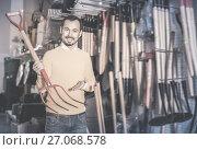Купить «Adult man choosing new pitchfork», фото № 27068578, снято 2 марта 2017 г. (c) Яков Филимонов / Фотобанк Лори