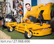 Купить «Man shows a large and powerful mulching mowers», фото № 27068606, снято 2 марта 2017 г. (c) Яков Филимонов / Фотобанк Лори