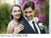 Купить «Beautiful bride with bridegroom standing in park», фото № 27069538, снято 2 мая 2017 г. (c) Wavebreak Media / Фотобанк Лори