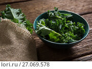 Купить «Mustard greens on wooden table», фото № 27069578, снято 12 июня 2017 г. (c) Wavebreak Media / Фотобанк Лори