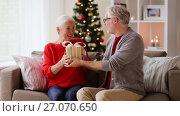 Купить «happy smiling senior couple with christmas gift», видеоролик № 27070650, снято 20 сентября 2017 г. (c) Syda Productions / Фотобанк Лори