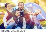 Купить «family with smartphone taking selfie at campsite», фото № 27083294, снято 27 сентября 2015 г. (c) Syda Productions / Фотобанк Лори