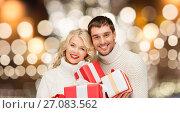 Купить «happy couple in sweaters holding christmas gifts», фото № 27083562, снято 7 октября 2012 г. (c) Syda Productions / Фотобанк Лори