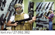 Купить «Young guy in military equipment with gun in airsoft shop», видеоролик № 27092382, снято 14 июля 2017 г. (c) Яков Филимонов / Фотобанк Лори