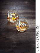 Купить «Close up view of two glasses with ice and whiskey on wooden background», фото № 27093154, снято 21 июля 2018 г. (c) Дмитрий Эрслер / Фотобанк Лори
