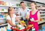 Smiling young woman with family choosing milk, фото № 27093866, снято 11 июля 2017 г. (c) Яков Филимонов / Фотобанк Лори