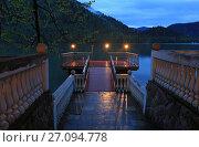 Купить «Таинственный вид на озеро Рица и пристань, освещенную фонарями в вечернее время», фото № 27094778, снято 8 мая 2017 г. (c) Яна Королёва / Фотобанк Лори