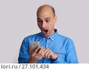 Купить «shocked guy reading Message on his smartphone», фото № 27101434, снято 3 августа 2017 г. (c) Александр Лычагин / Фотобанк Лори