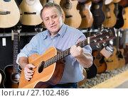 Купить «Adult man is playing on wooden acoustic guitar», фото № 27102486, снято 18 сентября 2017 г. (c) Яков Филимонов / Фотобанк Лори