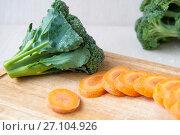 Купить «Raw carrot sliced and broccoli on a wooden board», фото № 27104926, снято 19 августа 2017 г. (c) Катерина Белякина / Фотобанк Лори