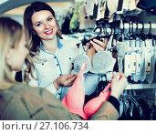 Купить «Female seller demonstrating client bras in underwear store», фото № 27106734, снято 20 марта 2017 г. (c) Яков Филимонов / Фотобанк Лори
