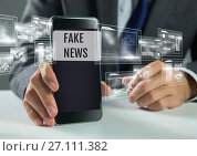 Купить «Holding phone with Fake news text and interface», фото № 27111382, снято 3 августа 2020 г. (c) Wavebreak Media / Фотобанк Лори