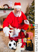 Купить «Santa claus placing gift box into gift sack at home», фото № 27125522, снято 6 сентября 2016 г. (c) Wavebreak Media / Фотобанк Лори