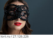 Купить «Woman wearing masquerade mask against black background», фото № 27126226, снято 22 мая 2017 г. (c) Wavebreak Media / Фотобанк Лори