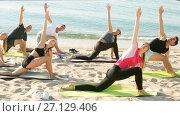 Купить «Group of sporty people practicing various yoga positions during training on beach», видеоролик № 27129406, снято 26 июня 2017 г. (c) Яков Филимонов / Фотобанк Лори