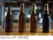 Купить «Arranged beer bottles on the bar counter», фото № 27130002, снято 22 августа 2017 г. (c) Wavebreak Media / Фотобанк Лори