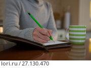 Купить «Mid section of woman writing in organizer», фото № 27130470, снято 10 августа 2017 г. (c) Wavebreak Media / Фотобанк Лори
