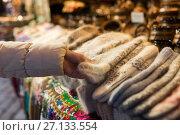 Купить «woman buying woolen mittens at christmas market», фото № 27133554, снято 1 декабря 2016 г. (c) Syda Productions / Фотобанк Лори