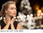 woman wearing jewelry over christmas lights. Стоковое фото, фотограф Syda Productions / Фотобанк Лори