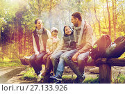 Купить «happy family sitting on bench and talking at camp», фото № 27133926, снято 27 сентября 2015 г. (c) Syda Productions / Фотобанк Лори