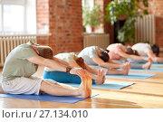 Купить «group of people doing yoga forward bend at studio», фото № 27134010, снято 5 марта 2017 г. (c) Syda Productions / Фотобанк Лори