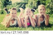 Купить «Happy kids laying on grass», фото № 27141098, снято 27 июля 2017 г. (c) Яков Филимонов / Фотобанк Лори