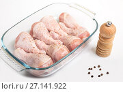 Купить «Chicken legs sprinkled with pepper in a dish for cooking on a white background», фото № 27141922, снято 23 октября 2017 г. (c) Юлия Бабкина / Фотобанк Лори