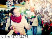 Купить «Female customer at the Christmas Fair», фото № 27142774, снято 27 марта 2019 г. (c) Яков Филимонов / Фотобанк Лори
