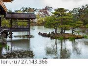 Купить «Мостки для ловли рыбы напротив маленького островка в водоеме. Золотой павильон (Kinkaku-ji). Дождь. Киото, Япония», фото № 27143366, снято 12 апреля 2013 г. (c) Кекяляйнен Андрей / Фотобанк Лори