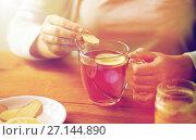 Купить «close up of woman adding ginger to tea with lemon», фото № 27144890, снято 13 октября 2016 г. (c) Syda Productions / Фотобанк Лори