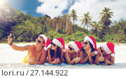 Купить «group of friends in santa hats with taking selfie», фото № 27144922, снято 3 августа 2014 г. (c) Syda Productions / Фотобанк Лори