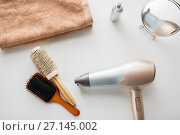 Купить «hairdryer, hair brushes, mirror and towel», фото № 27145002, снято 12 апреля 2017 г. (c) Syda Productions / Фотобанк Лори