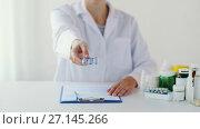 Купить «doctor showing pack of pills at hospital», видеоролик № 27145266, снято 21 июля 2018 г. (c) Syda Productions / Фотобанк Лори