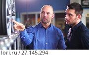 customer and salesman with car wheels at auto store. Стоковое видео, видеограф Syda Productions / Фотобанк Лори