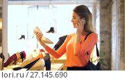 Купить «young woman calling on smartphone at shoestore», видеоролик № 27145690, снято 6 октября 2017 г. (c) Syda Productions / Фотобанк Лори