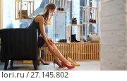 Купить «young woman trying heeled shoes at store», видеоролик № 27145802, снято 6 октября 2017 г. (c) Syda Productions / Фотобанк Лори